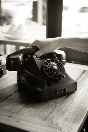 Woman using antique phone,black and white filtered.