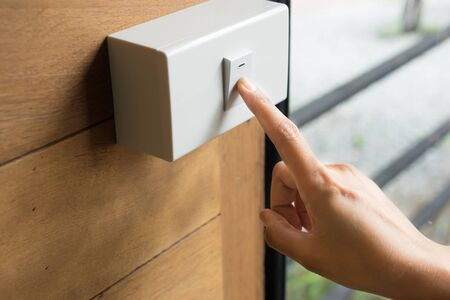 Woman finger is turning on or off light switch.