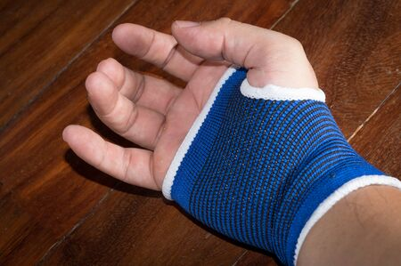 Male hand with blue wrist or palm support. Banque d'images