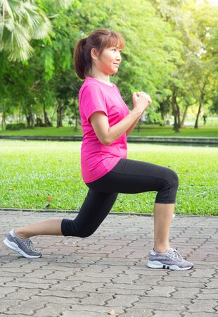 Woman doing lunge exercise in park. Standard-Bild