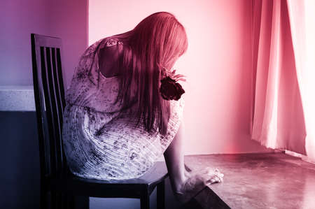 sad girl sit on chair, multi color filtered. Stock Photo