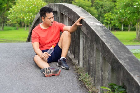 Asian man tired or fail from running exercise.