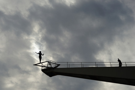 disheartened: Ballance unter dem Himmel. Schattenriss einer Frau auf einem hohen Kran.