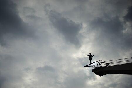 Ballance unter dem Himmel. Schattenriss einer Frau auf einem hohen Kran.