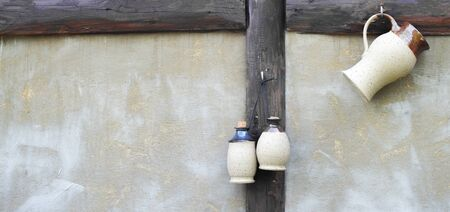 jugs: Three white jugs hanging on the wall