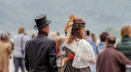 latter: A couple in clothes of the 19th century. It seems like time travelers, as all others are clothed latter day.