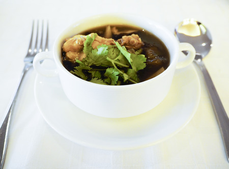 Fish maw soup in a white bowl with silver cutlery Stock Photo