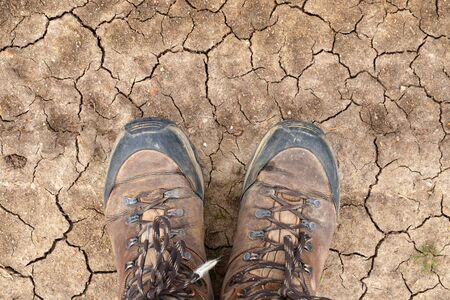 Young man walking the Way of St James, standing in his hiking boots on a dry desert soil in Castilla y León, Spain