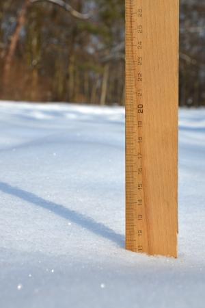 centimetres: A ruler in the snow measuring 11 centimetres depth Stock Photo
