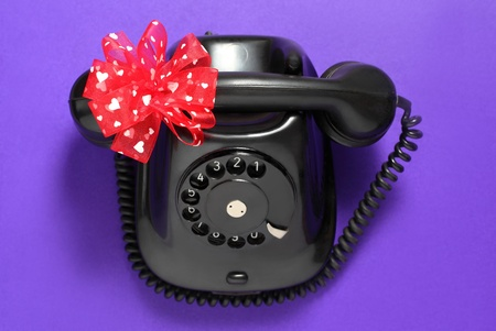 Old-fashioned phone isolated on a purple background with red ribbon with white hearts.  photo