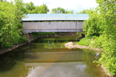 covered bridge: Covered Bridge reflecting in River