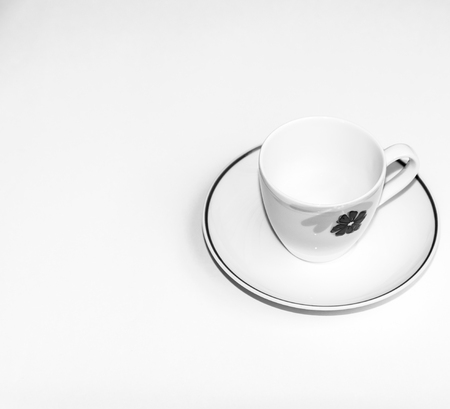 decaffeinated: Cup of coffee beans with a spoon and saucer on a white background with the outline of more coffee beans
