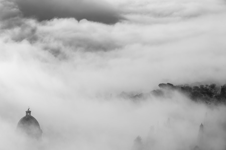 immersed: Church of Cortona immersed in fog in Tuscany - Italy Stock Photo