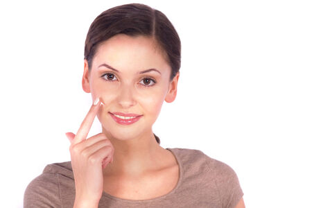 Portrait of a young woman applying cream on her face  photo