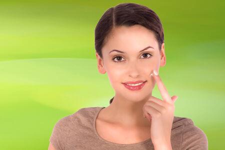 Beautiful woman cream her face photo