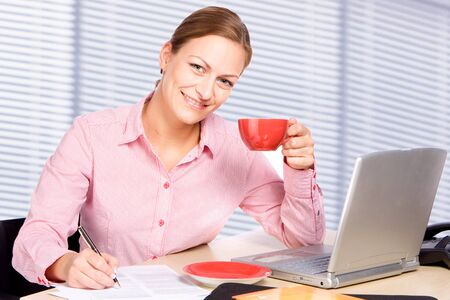 professionally: Woman with cup in her hand at her office desk
