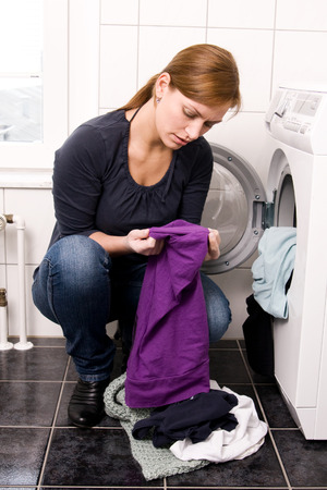 powder room: Young woman doing her laundry Stock Photo