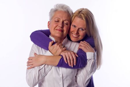 intimately: younger woman give a hug to the older one Stock Photo