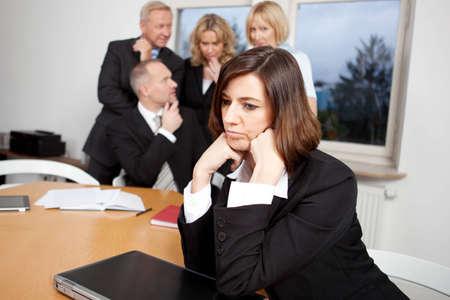 blasphemy: Sad businsesswoman with team in the background