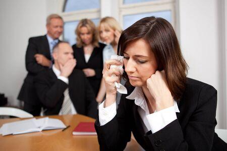 blasphemy: Sad businesswoman with team in the background