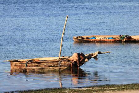rigger: Man repairing out-rigger fishing canoe Editorial