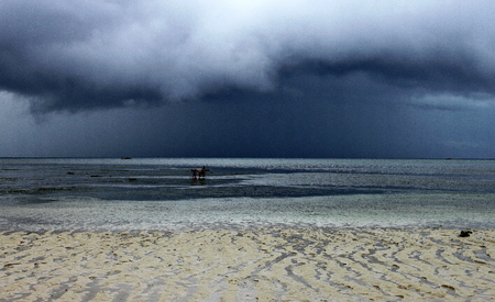 Islanders harvesting the sea at low tide before a storm photo