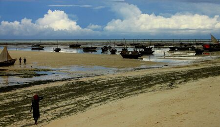 subsistence: Woman walking towards fishing dhows at low tide Stock Photo