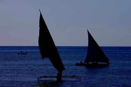austere: Outrigger sails silhouetted in the moonlight Stock Photo