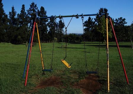 Not in working order - broken swing in play park Stock Photo