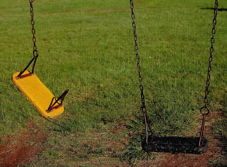 'odd one out': Not in working order - broken swing in play park Stock Photo
