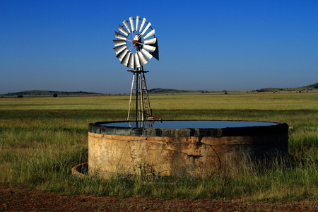 Windmill and a small dam on open farm land Stock Photo