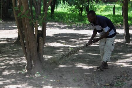 destitute: Rural living - villager sweeps using a broom made from grass - Mozambique Editorial