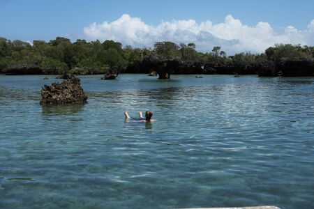 zanzibar: Travel - Woman swimiing in the azure water off Zanzibar Editorial