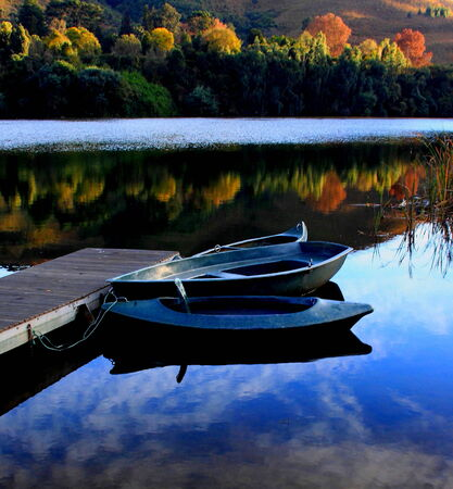 sunup: Canoes moored on a country pond with autumn reflectios on the water Stock Photo