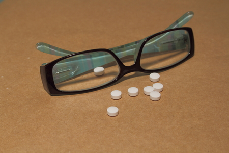 Reading glasses and pills - a stage in the cycle of life Stock Photo