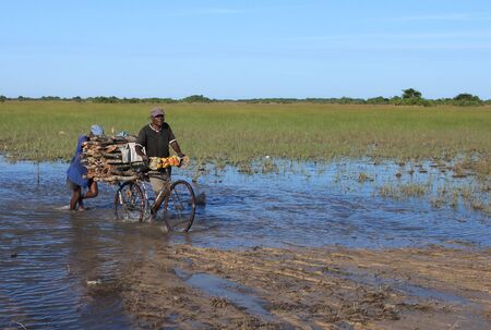 Rural living - villagers cross a flooded road in Mozambique, Africa
