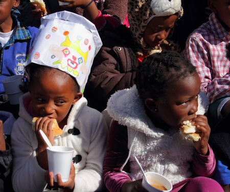 underprivileged: Poor school children being fed in winter Gauteng South Africa
