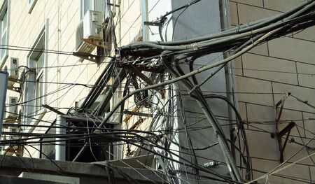 untidy: Untidy cables on the side of a building