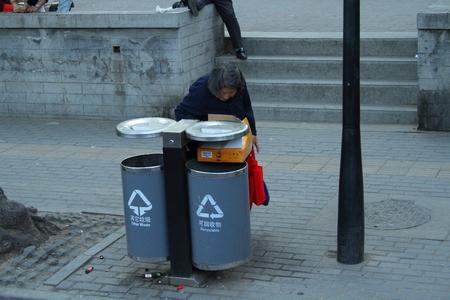 impoverished: Homeless woman searching in refuse bin Xian China