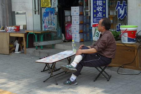 selfemployed: Shopkeeper sits outside his shop Xian China Editorial