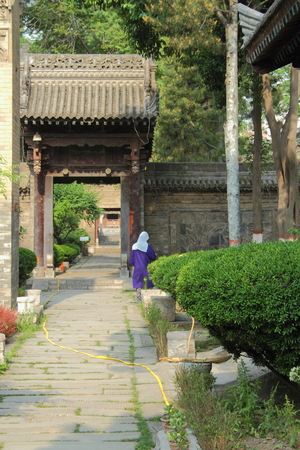 working woman: Woman working in garden of ancient temple