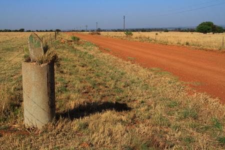 distance: Distance marker next to a dirt road