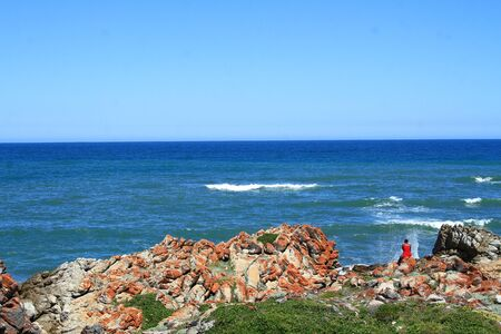 horison: Person in red top sitting on the rocks next to the sea