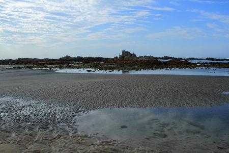 botas altas: Arena y rocas expuestas durante la marea baja Foto de archivo