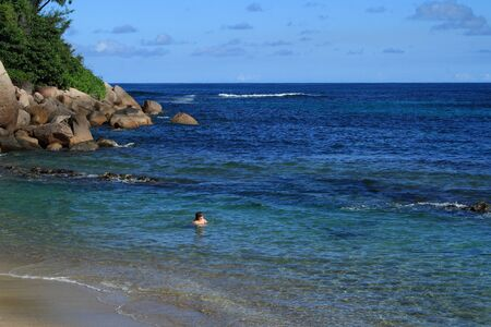 holidaymaker: Woman swimming on a secluded beach on a tropical island