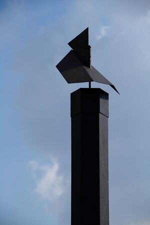 flue: A black chimney with weather vane against a clear blue sky Stock Photo