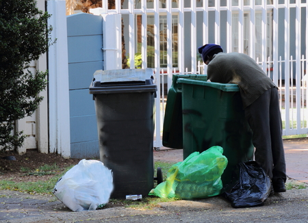 homeless person: Poor, homeless person searching through residential rubbish bins Editorial