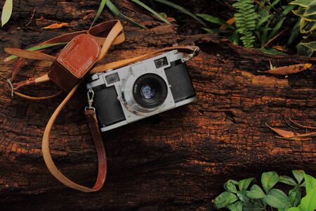 days gone by: Retro 35 mm camera on a rough log Stock Photo