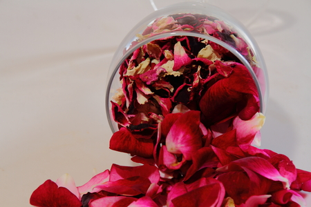 knocked over: Pink rose petals spill from a fallen wine glass