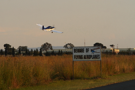 Microlight aircraft flying over a contradicting warning sign